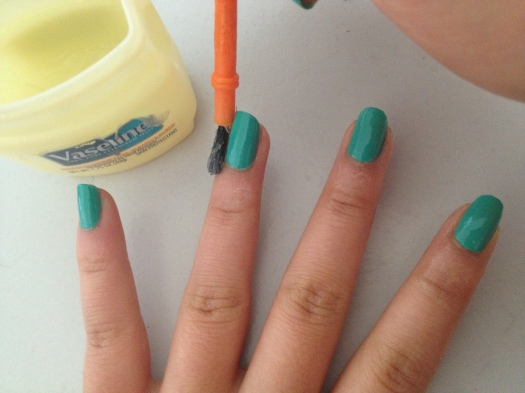 Step 4: Use a small brush or a q-tip to paint a layer of Vaseline around your nail. I went up to the first knuckle. This step is essential! Don't forget to cover the pads of your fingers too. You could use tape as well.